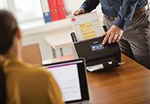 En mann på et kontor skanner et dokument på en Brother ADS3600W skanner