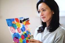 En kvinne holder et fargerikt utskrevet dokument