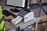 muž ve výstražné vestě tiskne ve skladu štítky na tiskárně Brother TD-4520DN
