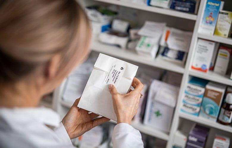 Medicine bag being labelled in pharmacy
