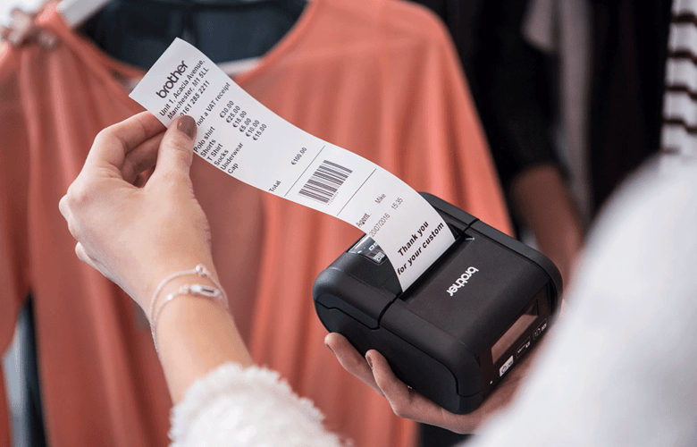 Female store assistant hands printing receipt from RJ printer in clothes shop