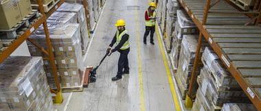 Deux professionnels travaillant dans une entreprise de transport et logistique en train de manipuler une palette de marchandises