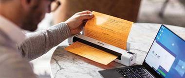 Un homme travaille sur son ordinateur et utilise un scanner portable pour numériser un document