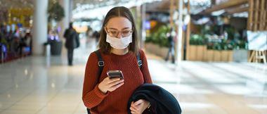 Une jeune femme se promenant dans un centre commercial consulte son smartphone tout en portant un masque.