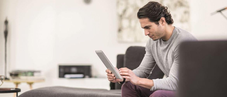 Un homme travaillant chez lui depuis son canapé consulte une tablette et l'on peut apercevoir une imprimante Brother Mini-17 DCP-J772DW en arrière plan