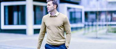 Un homme marche seul devant un ensemble de bâtiments.