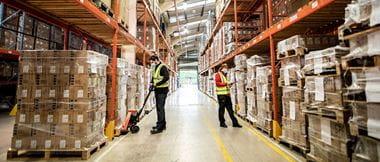 Deux préparateurs de commandes travaillent ensemble au sein d'un entrepôt.