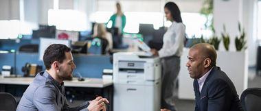 Deux hommes discutent au sein d'un bureau tandis qu'une collègue utilise une imprimante en arrière-plan