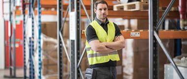 Jeune homme croisant les bras dans un entrepôt