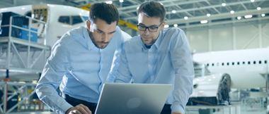 Deux professionnels travaillant à distance, sont penchés sur un ordinateur portable, dans un hangar d'aviation.