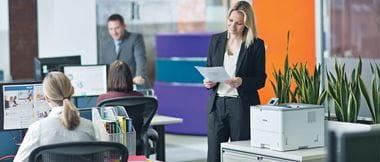 Une femme souriante se tient près d'une imprimante sur son lieu de travail, tout en tenant un document qu'elle vient d'imprimer.