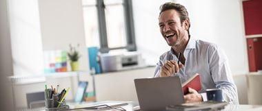 Un homme de bonne humeur travaille à son bureau, équipé d'un ordinateur portable et d'une imprimante wifi.