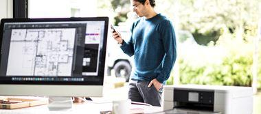 Une employé regarde son smartphone. Au premier plan, son bureau équipé d'un ordinateur et d'une imprimante Brother.
