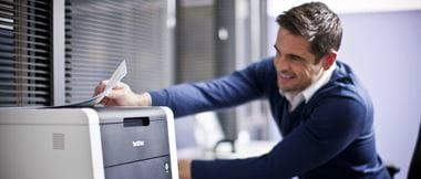 Un homme récupère ses documents imprimés auprès d'une imprimante de marque Brother