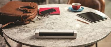 Un scanner Brother sur une table avec des accessoires pour travailler