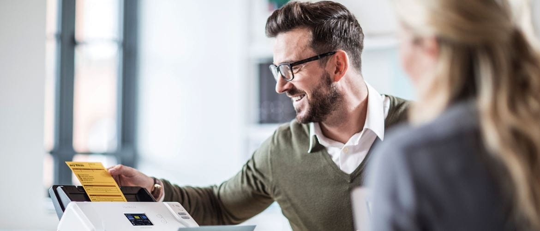 Un homme se tenant aux côtés d'une femme utilise en souriant un scanner pour numériser un document