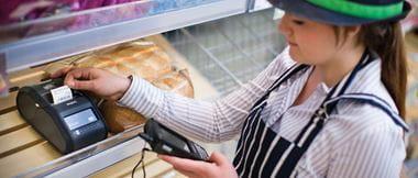 Une jeune femme travaillant pour un commerce alimentaire imprime une étiquette à l'aide d'une imprimante d'étiquettes portable de marque Brother