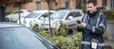 Un agent équipé d'une imprimante d'étiquettes dresse une contravention dans la rue