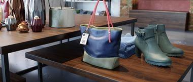 Un sac à main avec une étiquette de prix de vente est exposé dans un magasin de détail à côté d'une paire de chaussures