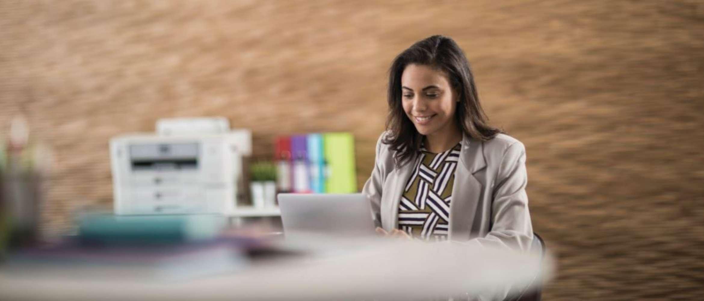 Une jeune femme souriante travaillant sur son ordinateur portable, au sein d'un environnement comprenant des classeurs et une imprimante de marque Brother