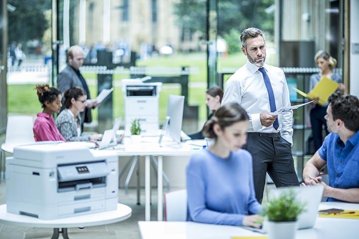 Plusieurs personnes travaillant au sein d'un bureau lumineux de type open space  équipé de plusieurs ordinateurs portables et d'imprimantes multifonctions.