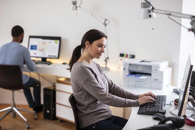 Un femme et un homme partagent un espace de travail lumineux, avec entre eux une imprimante Brother