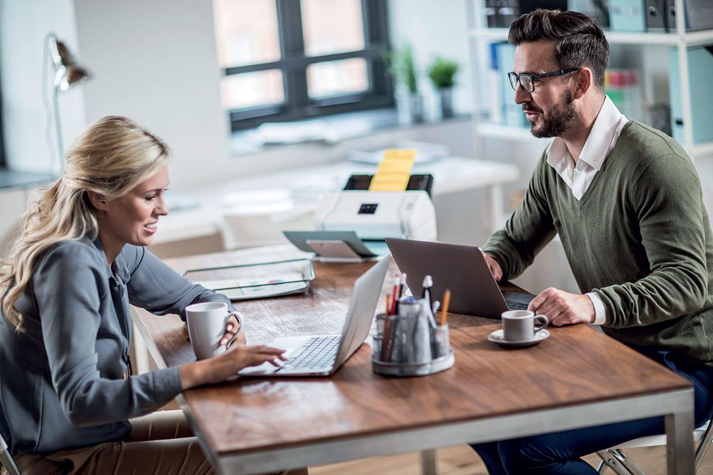 Un homme et une femme travaillent ensemble autour d'une table, avec en arrière plan un scanner Brother.