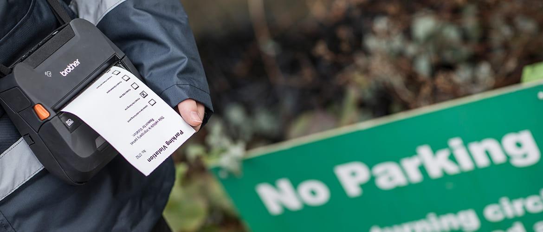 Un agent tenant une imprimante portable RJ de Brother en bandoulière imprime un ticket.