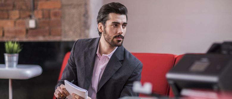 Un homme assis prend des notes à l'aide d'un bloc de papier tandis qu'au premier plan se trouve un scanner Brother ADS conçu pour le travail à domicile.