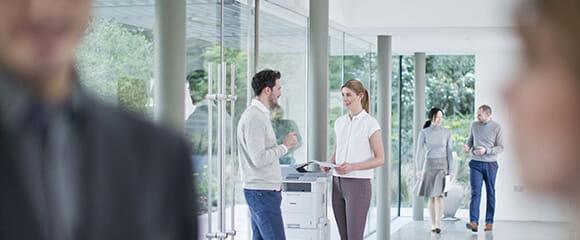 Deux salariés de Brother discutant devant une imprimante multifonctions
