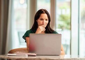 Une femme cherche de l'aide pour trouver la bonne imprimante Brother sur l'aide au choix en ligne