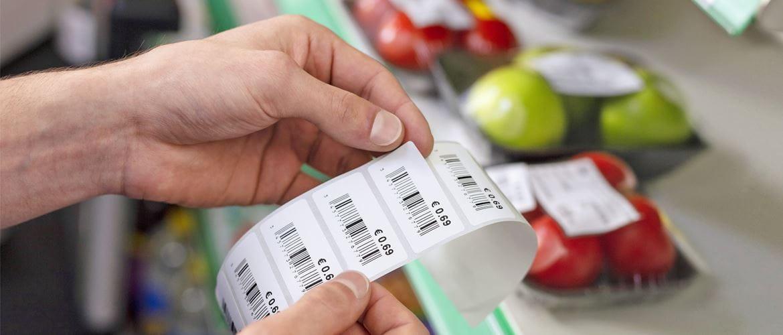 Main décollant une étiquette de prix avec code-barres dans une épicerie avec des pommes et des tomates en arrière-plan.