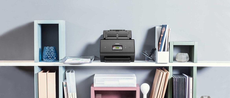 Scanner de documents de bureau ADS-3600W posée sur une étagère avec des ordinateurs portables