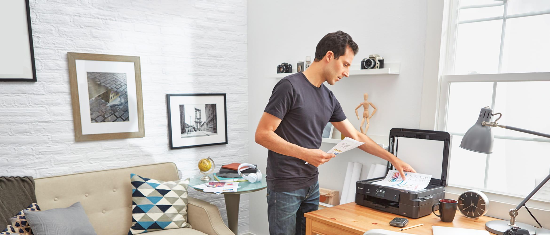 un homme à la maison numérisant des documents à l'aide d'un scanner Brother