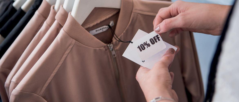 Client regardant une étiquette de vêtement sur un portant