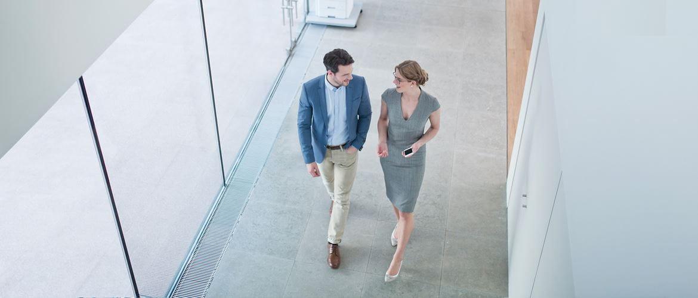 deux collègues discutant dans un couloir de l'entreprise