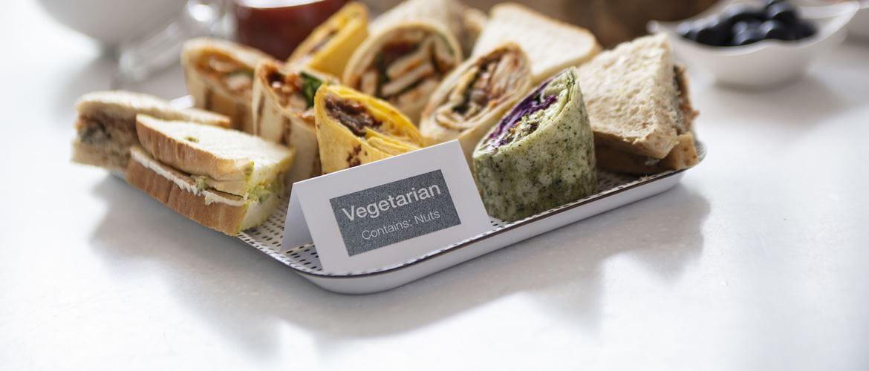 Carton étiqueté posé devant un plateau d'aliments identifiant les aliments et les allergènes