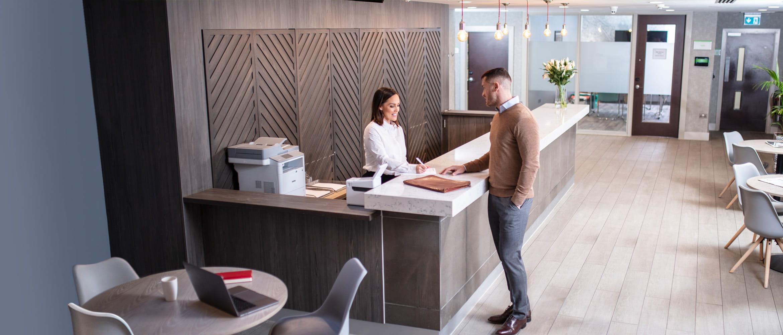 Une hôtesse d'accueil discute avec le client dans l'hôtel. Une imprimante Brother est sur le bureau à côté de l'hôtesse.