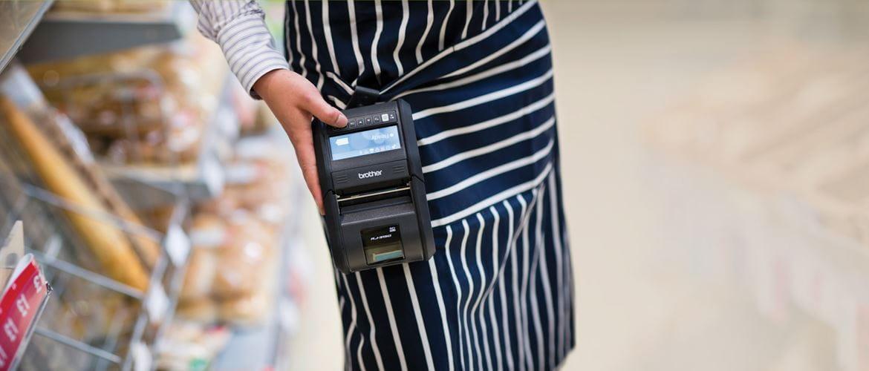 Personnel de vente au détail portant l'imprimante mobile de Brother RJ-3150 en magasin