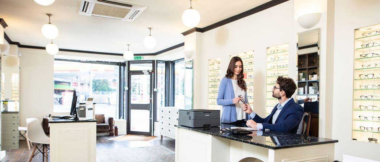 Un opticien assis en costume et une vendeuse en cardigan lila observent des paires de lunettes. Une imprimante Brother est disposée sur le bureau.