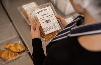 Femme portant un tablier rayé bleu et blanc tenant un produit de boulangerie conditionné dans une boîte en plastique avec une étiquette collée dessus