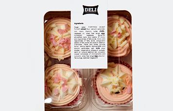 Petits gâteaux roses et blancs dans une boîte en plastique transparente avec une étiquette indiquant les ingrédients