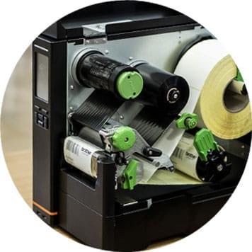 Imprimante ouverte, rouleau d'étiquettes blanches, mécanismes verts, rouleaux