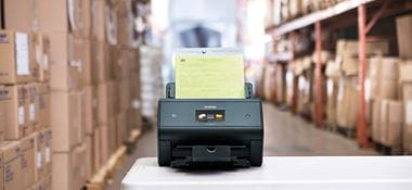 Scanner de bureau Brother ADS-3600W posé sur une table dans un entrepôt avec à côté de nombreux cartons sur des étagères