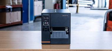 Une imprimante d'étiquettes industrielles noires posée sur une table dans un entrepôt