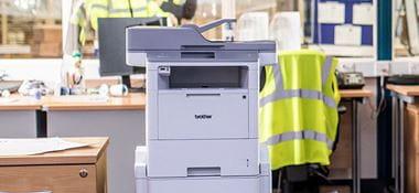 Imprimante Brother posé au sol dans le bureau de l'entrepôt, gilet de sécurité, fenêtre, paperasserie