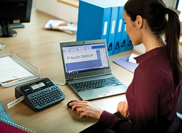 une femme regardant à l'écran de son ordinateur portable avec ses lunettes de vue à la main
