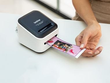 L'imprimante d'étiquettes couleur Brother qui imprime une large étiquette avec clip art et photo