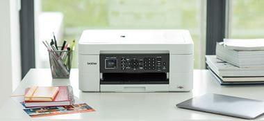 DCP-J572DW Brother imprimante jet d'encre posée sur bureau blanc, ordinateur portable, pot à crayons avec stylos, carnets de notes