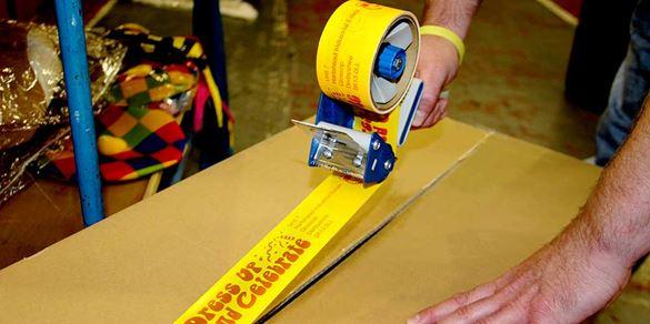 Un employé d'entrepôt ferme un carton avec du ruban d'emballage personnalisé créé sur Brother Tape Creator Pro